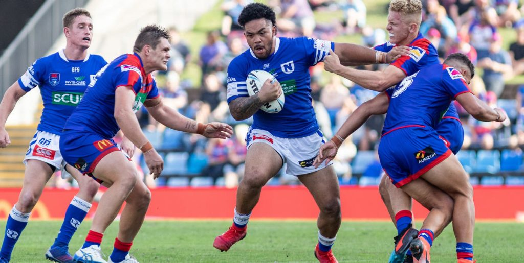Strongly-built Newtown Jets forward Siosifa Talakai is on the rampage as he takes on these Newcastle Knights defenders at the McDonald Jones Stadium on Friday afternoon (!5th March). Jets halfback Jack A. Williams is on the left of this image. Photo: Mario Facchini, mafphotography