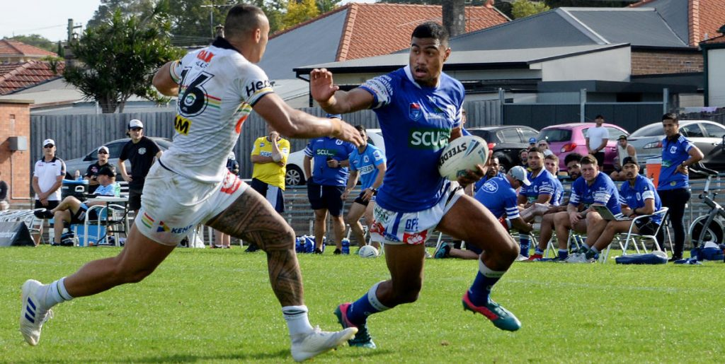 Newtown Jets centre Ronaldo Mulitalo is try-line bound as he fends off a Penrith Panthers opponent in the last minute of play at Henson Park on Sunday. Photo:  Michael Magee Photography.