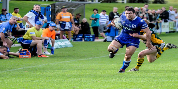 Newtown Jets centre Josh Davis shows admirable determination as he tries to beat this Wyong Roos defender last Sunday.