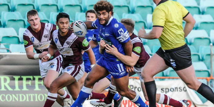 Newtown Jets backrower Junior Roqica looks to get his pass away after making a strong run through the Manly Sea Eagles defensive line. Photo: Gary Sutherland Photography