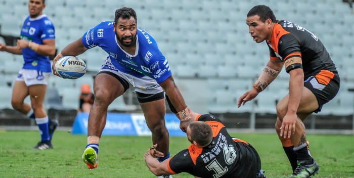 "Giant Newtown Jets forward Tony ""The T-Rex"" Williams pushes away a would-be Wests Tigers defender in last Saturday's exciting ISP NSW match at Campbelltown Stadium. Photo: Gary Sutherland Photography"