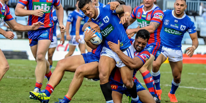 Fa'amanu Brown looks to break through the attempted tackles of these Newcastle Knights defenders in the 2017 5th Round ISP NSW match played at Southern Cross Group Stadium on the 1st April. Photo: Gary Sutherland Photography.