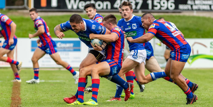 Newtown Jets prop Braden Uele ploughs through the Newcastle Knights defence on Saturday afternoon, with halfback Kyle Flanagan close by in support. Photo: Mario Facchini (MAF Photography)