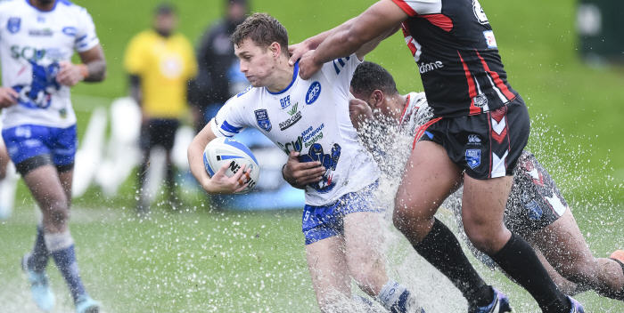 Newtown Jets five-eighth Jack A. Williams is collared by the New Zealand Warriors defence in slightly damp conditions in Auckland on Saturday afternoon. Photo: Photosport NZ