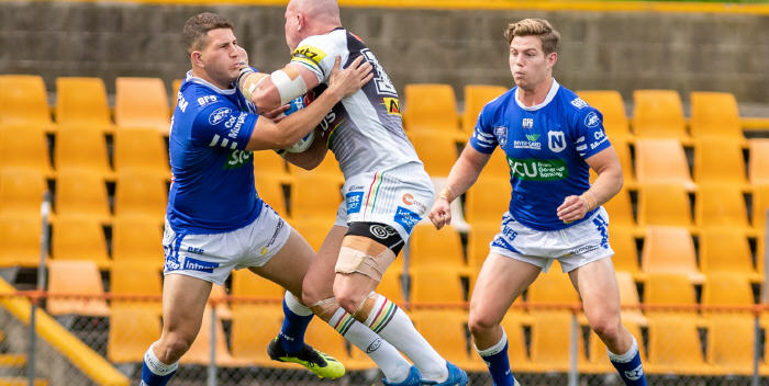 Gigantic Penrith Panthers prop Andy Saunders can't get past Newtown Jets defenders Billy Magoulias (left) and Blayke Brailey at Leichhardt Oval on Saturday afternoon. Photo: Mario Facchini, mafphotography