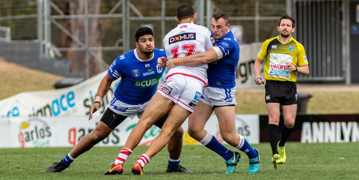 Newtown Jets forwards Malakai Houma (left) and Jimmy Jolliffe wrap up this St George-Illawarra player at Panthers Stadium on Sunday. Photo: Mario Facchini, mafphotography