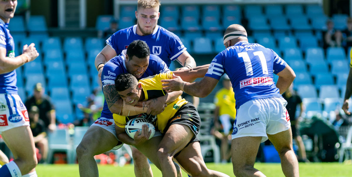 This Mounties Canterbury Cup player is well covered by these Newtown Jets players at Shark Park on Saturday. From the left: Kyle Flanagan, Wes Lolo (making the tackle), Daniel Vasquez (at rear), Anthony Moraitis (number 11). Photo: Mario Facchini, mafphotography