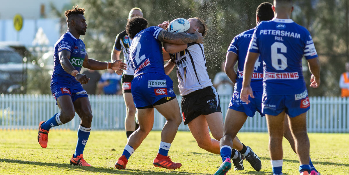 The sweat flies as Newtown second-rower Siosifa Talakai makes solid body contact with a Wentworthville opponent on Sunday. The other Jets players are (from left) James Segeyaro, Ronaldo Mulitalo and Braydon Trindall. Photo: Mario Facchini, mafphotography