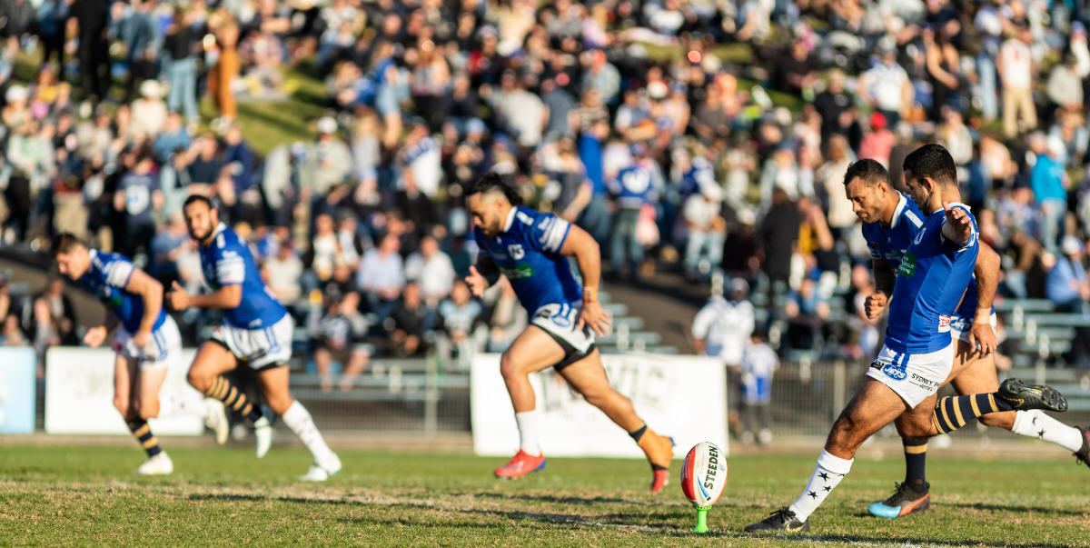 Newtown Jets hooker Braydon Trindall gets the second half underway at Henson Park on Saturday, with the colossal BF&F Festival crowd looming in the background. Photo: Mario Facchini, mafphotography