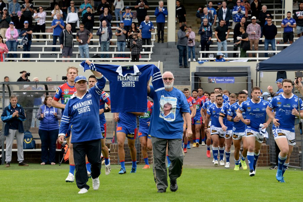 Two outstanding identities with many years of association with the Newtown RLFC, Colin Murphy (left) and Johnny Lewis, lead the teams out at Henson Park on Saturday while carrying a number seven jersey in honour of the late Tom Raudonikis.     Photo: Michael Magee Photography.