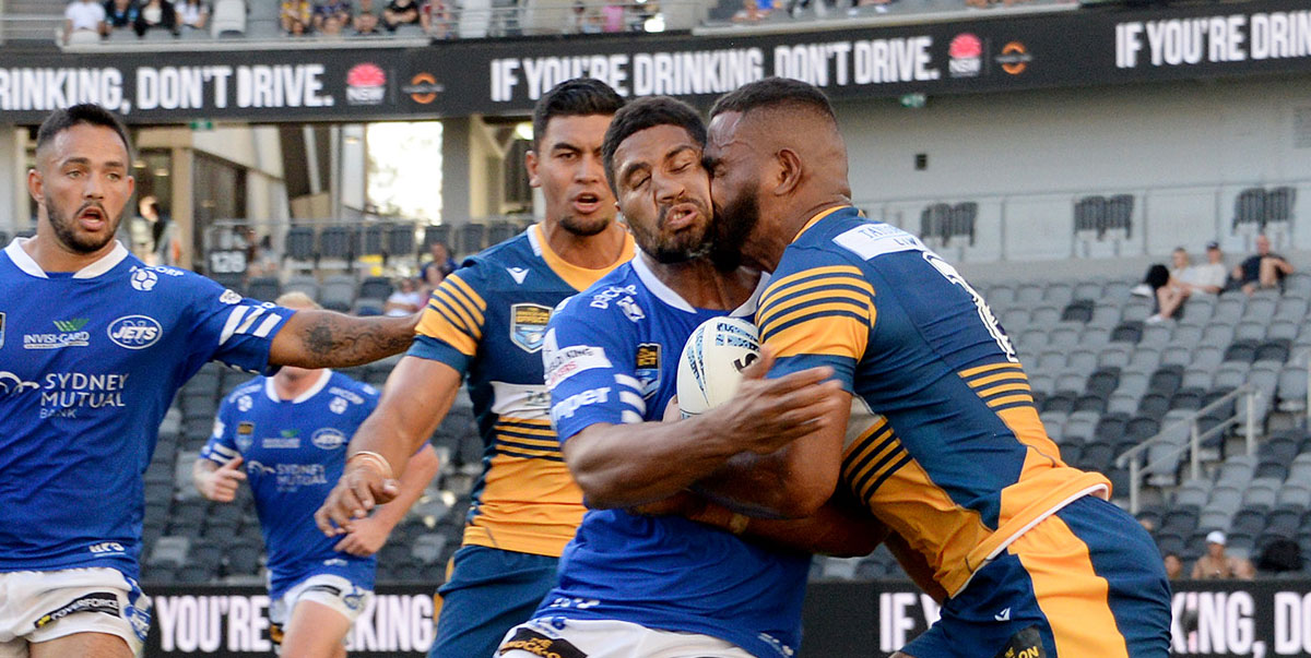 Photo caption: Newtown Jets winger Nene Macdonald comes to close quarters with a Parramatta opponent in last Saturday's match against Parramatta.     Photo: Michael Magee Photography.