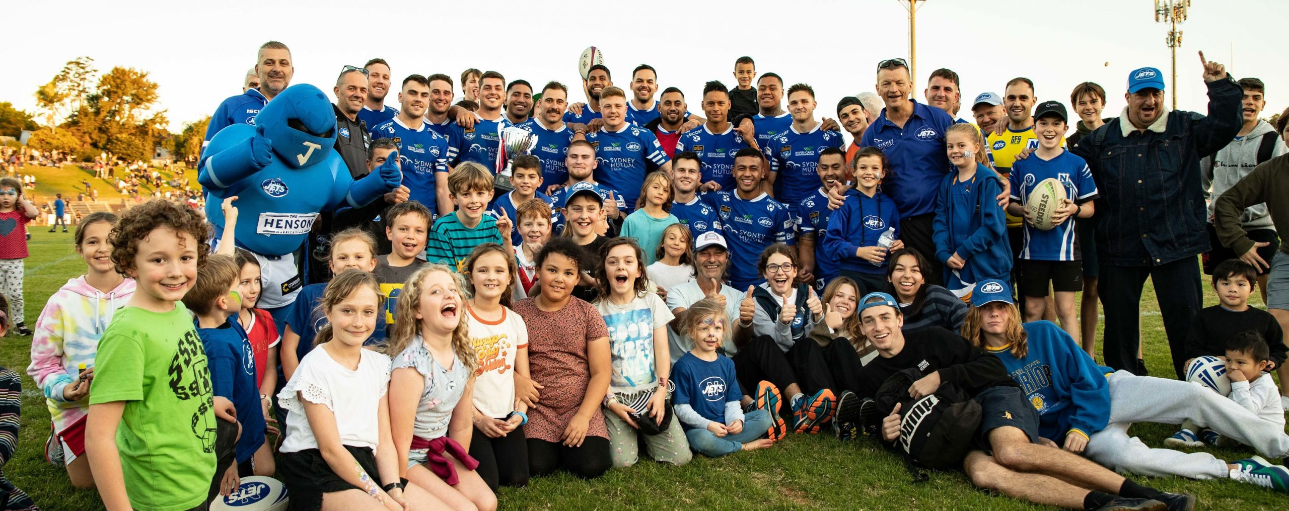 All good friends and jolly good company … the Newtown Jets players, team staff, the other-worldly Jetman and a few young supporters get together to celebrate winning the Tom Kirk Cup against St George-Illawarra at Henson Park last Saturday.     Photo: Mario Facchini, mafphotography