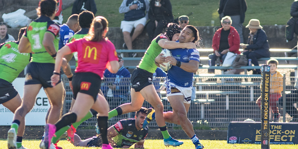 Photo caption: Jets winger Edward Aiono is on the receiving end of a high one from a Raiders defender, as he charges in to score Newtown's first try on Saturday at Henson Park.     Photo: Mario Facchini, mafphotography